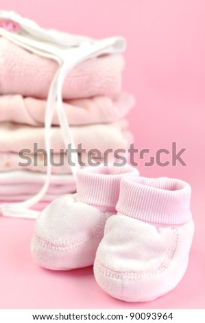 Booties, and a pile of pink baby laundry - stock photo