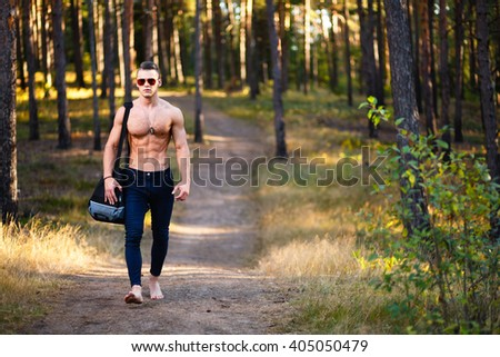 Bootlessly muscular young man with bag in a forest. - stock photo