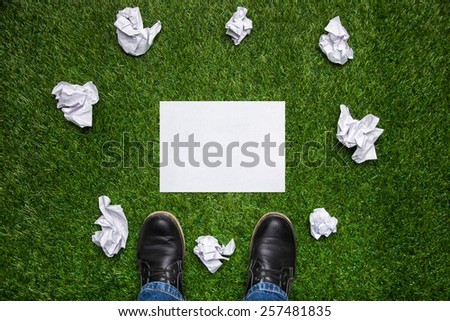 Boots and sheet of paper with cramled sheets on the grass - stock photo