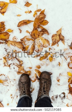 Boots legs view on the snow with fallen leaves at autumn fall winter season