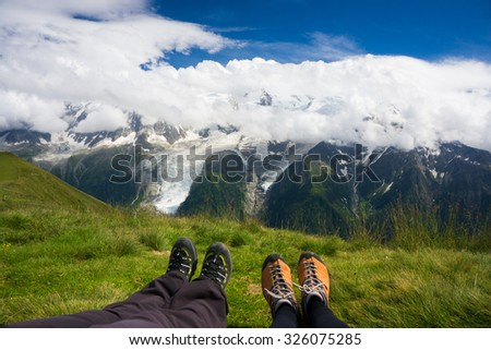 Boots of a couple (man and woman) sitting in the mountains admiring the view of Mont Blanc from Aiguilles Rouges natural Reserve - stock photo
