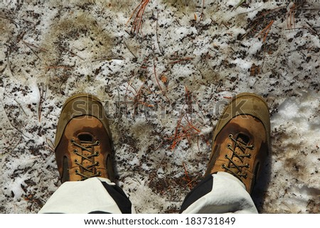 boots on the melt snow in spring - stock photo