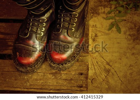 Boots on wooden planks, vintage style, top view - stock photo