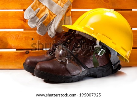 Boots, yellow hard hat, goggles, gloves on the background boards - stock photo