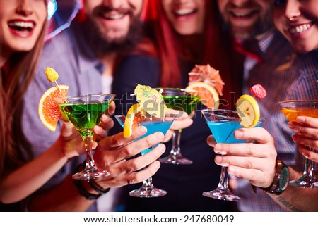 Boozing friends cheering up with cocktails at party