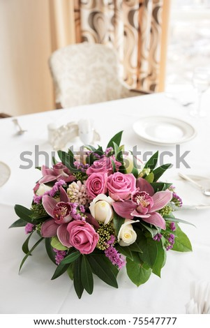 Boquet of orchid flowers and tulips on arranged table - stock photo