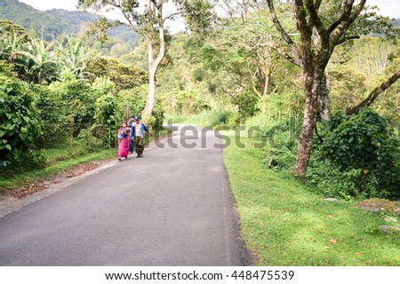Boquete, Panama - August 23, 2015: Indigenous family from the Ngabe-Bugle tribe walks the road through the caffeinated highlands of Boquete, Chiriqui region, Panama - stock photo