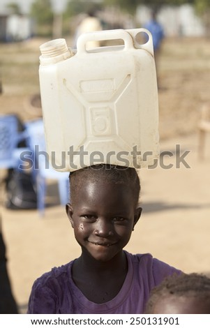 BOR, SOUTH SUDAN-DECEMBER 3, 2010: Unidentified child carries a large water container on her head. - stock photo