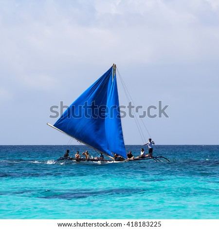 Boracay Island, Philippines - 11 November 2011: Local wooden sailing boat at the sea with people