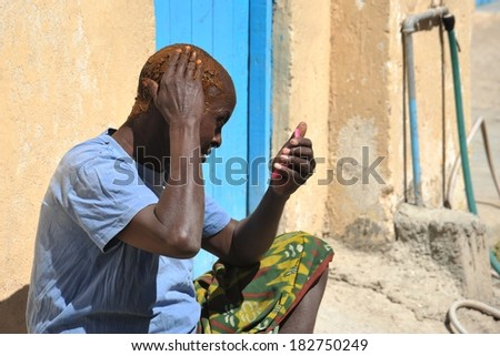 BORAMA, SOMALIA - JANUARY 13, 2010:  Old Somali dye his hair with henna in the street of the city of Borama. Located near the border with Ethiopia. Much of the population lives in poverty.