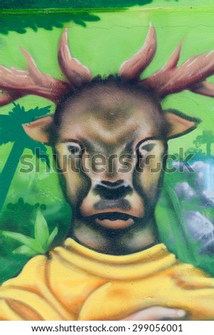 BORDEAUX, FRANCE â?? June 23, 2015: Graffiti art â?? Man with a deers head and antlers portrait in the forest on a fence in the city suburbs.