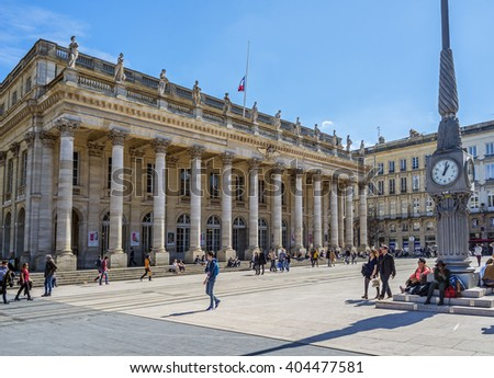 Bordeaux, France - March 26, 2016. People walking in front of Grand Theatre de Bordeaux at sunny day. The theatre is home to the Opera National de Bordeaux and the Ballet National de Bordeaux. - stock photo