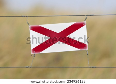Border fence - Old plastic sign with a flag - Alabama - stock photo