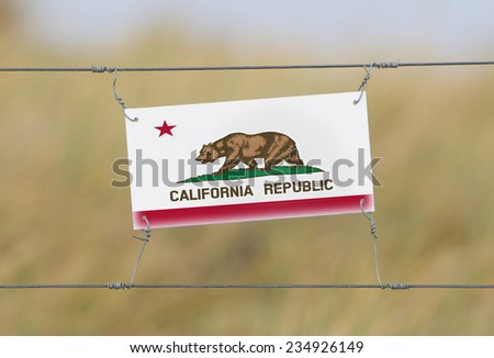 Border fence - Old plastic sign with a flag - California - stock photo