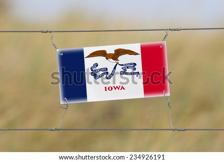 Border fence - Old plastic sign with a flag - Iowa - stock photo