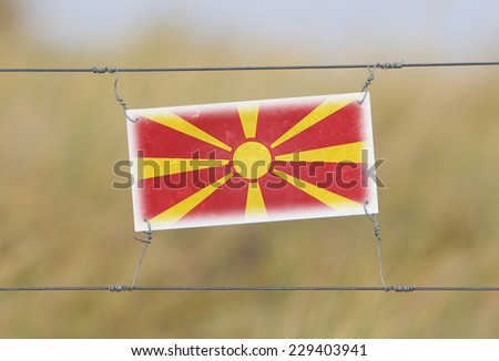 Border fence - Old plastic sign with a flag - Macedonia - stock photo