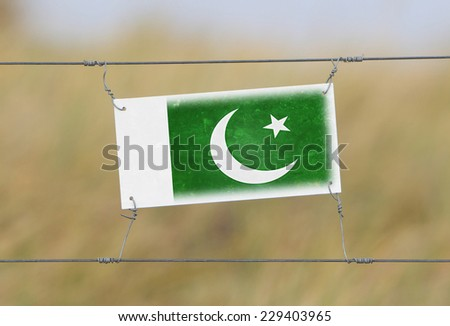 Border fence - Old plastic sign with a flag - Pakistan - stock photo