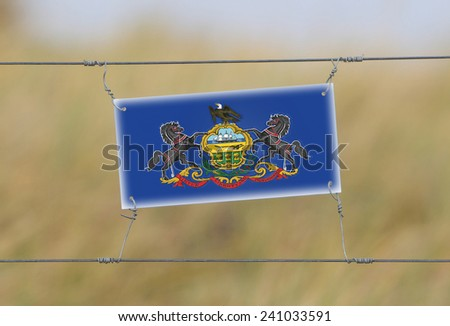 Border fence - Old plastic sign with a flag - Pennsylvania - stock photo