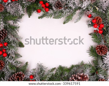 Border, frame from christmas tree branches with pine cones and holly berries