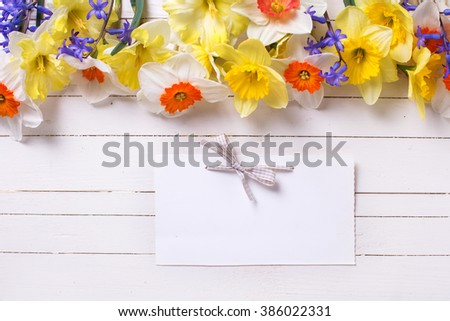 Border from colorful yellow, orange and blue spring flowers and empty tag on white  painted wooden planks. Selective focus. Place for text.  - stock photo