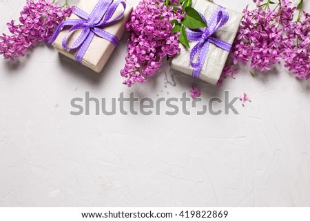 Border from wrapped  gift boxes with presents  and lilac flowers on grey textured background. Selective focus. Place for text. - stock photo