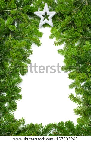 Border made of fresh green fir twigs creating the empty shape of a Christmas tree - stock photo
