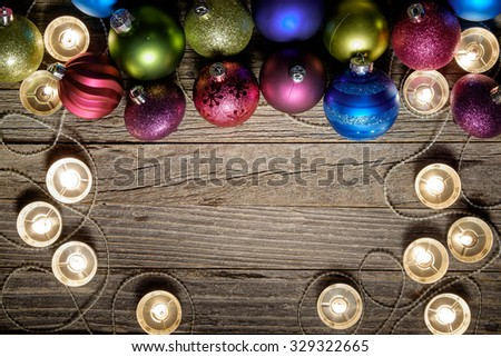Border of Christmas colorful balls and candles on an old wooden background, copy space for text, top view.