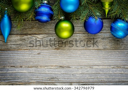 Border of Christmas fir tree branches with blue and green ornaments on an old wooden board, copy space for text, top view.