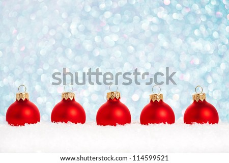 Border of Christmas tree decorations in snow against lights background - stock photo