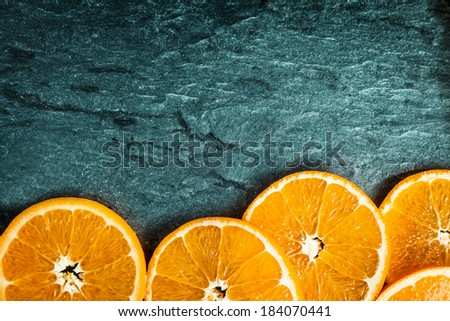 Border of colorful fresh juicy orange slices on a textured slate background with copyspace and vignetting - stock photo