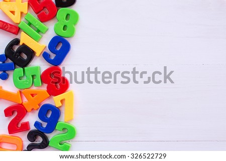 Border of colorful toy magnetic numbers with copy-space on wooden background - stock photo