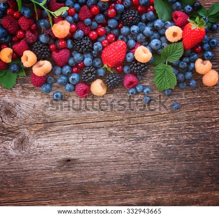 border of fresh  berries mix on wooden tabletop with copy space, retro toned - stock photo