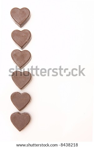 border of little chocolate hearts isolated on white