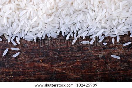 Border of long grain white rice on wood background - stock photo