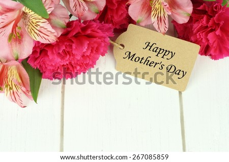 Border of pink carnation and lily flowers with Happy Mother's Day gift tag on white wood background - stock photo