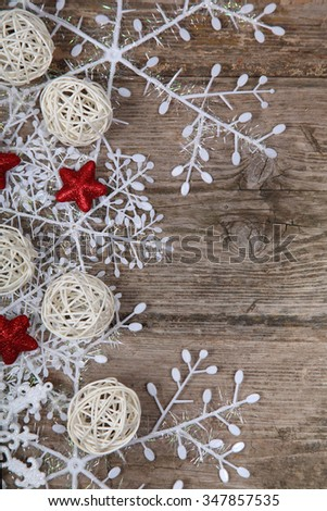 Border of snowflakes and Christmas decoration on the wooden background