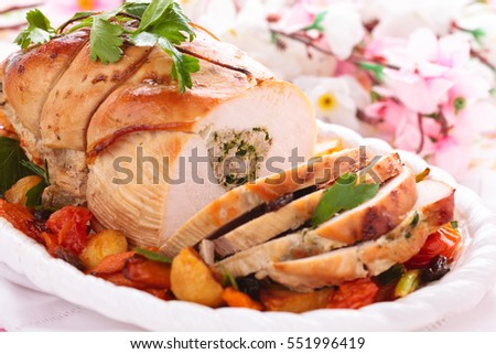 Border of stuffed turkey breast with baked vegetables, parsley and spices on plate.
