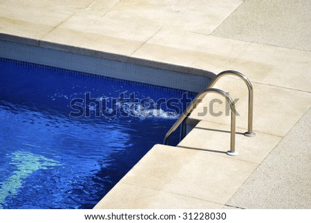 Border of the pool with metallic stairs