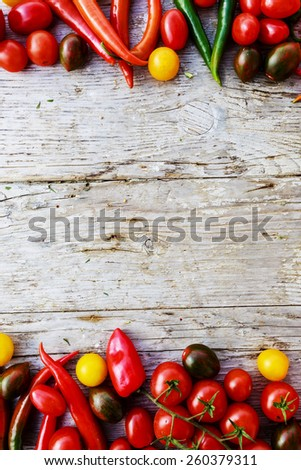 Border of tomatoes and paprica family varieties over a rustic wooden background with copyspace - stock photo
