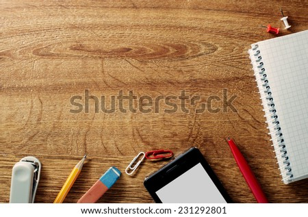 Border of various office supplies and stationery over a textured wood background with a notebook, pencil, eraser, paperclips, tablet, pen, stapler and thumbtacks along the lower edge of the frame - stock photo