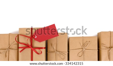 Border row of brown paper parcels, one unique with red ribbon bow and gift tag  - stock photo