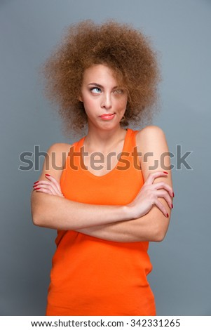 Bored annoyed curly pretty young woman looking up and posing with crossed arms on gray background - stock photo