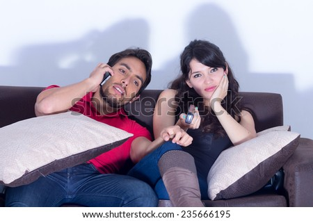 bored annoyed girlfriend watching television while boyfriend chats on the phone