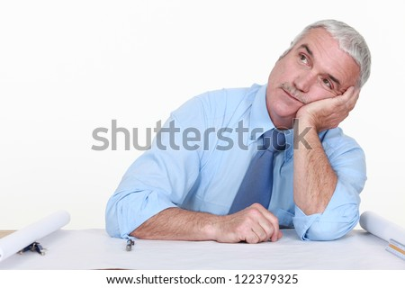 Bored architect staring off into space - stock photo