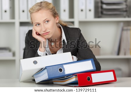 Bored blond businesswoman with stack of binders in office - stock photo