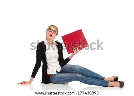 Bored blond young woman in nerd glasses sitting on the floor, holding ring binder and looking up with open mouth. Full length studio shot isolated on white. - stock photo