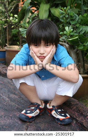 Bored boy squatting and holding his face in the park - stock photo