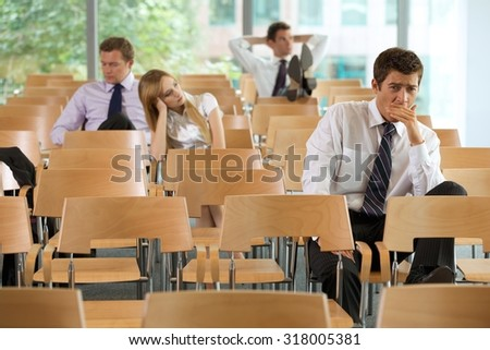 bored Business executives sitting in conference room - stock photo