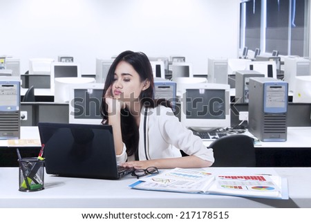 Bored business woman working with laptop in office - stock photo