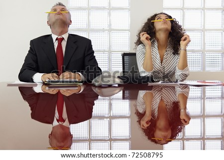 Bored businessman and secretary playing with pencil and having fun in office meeting room. Horizontal shape, front view, waist up - stock photo